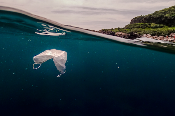 Disposable plastic mask floating in the sea